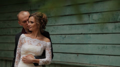 Beautiful wedding couple near a blue wall Stock Footage