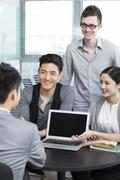 Office workers inviting businessman using laptop Stock Photos