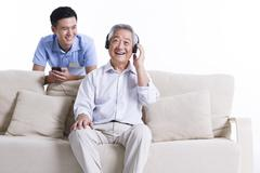 Senior man listening to music with nursing assistant's company Stock Photos