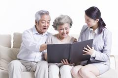 Senior couple chatting with financial advisor - stock photo