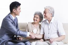 Senior couple shaking hands with financial advisor - stock photo