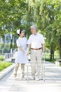 Senior man walking with walking frame under nurse's assistance - stock photo