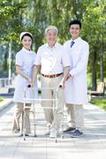 Senior man  walking with walking frame under doctor and nurse's assistance - stock photo