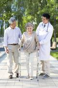 Senior woman walking with walking frame under doctor and  husband's assistance - stock photo