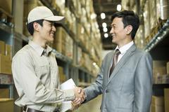 Stock Photo of Young logistics staff shaking hands with businessman