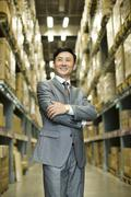 Stock Photo of Confident businessman arms crossed in logistic warehouse