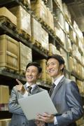 Stock Photo of Business partners with laptop in logistic warehouse