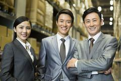 Confident business people in warehouse - stock photo