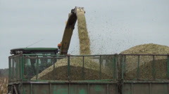 Follow closeup of combine harvester load harvested corn to truck Stock Footage