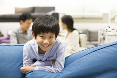 Cheerful boy in furniture shop with parents Stock Photos