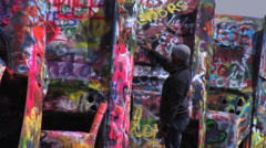 Painting Cars at Cadillac Ranch - Amarillo, Texas Stock Footage
