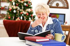 christmas: senior woman looks at photo albums - stock photo