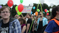 Crowd flock gay parade members multi colored balloons and flags Stock Footage