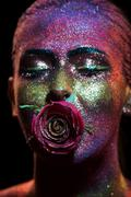Glitter makeup on a beautiful woman face on a black background Stock Photos