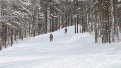 Skiers ski down shaded run Stock Footage