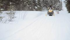 Snowmobilers pass camera on trail Stock Footage