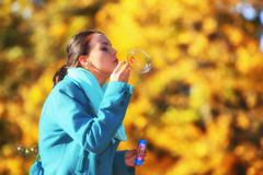 Young woman having fun blowing soap bubbles in autumnal park Stock Photos