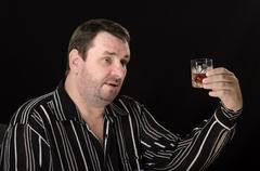 Stock Photo of mature guy has tost with glass of brandy