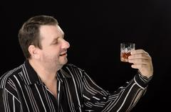 Stock Photo of man with a love watching glass brandy