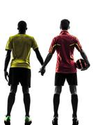 Stock Photo of two men soccer player  standing hand in hand silhouette