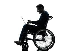 Handicapped man computing laptop computer  in wheelchair silhouette Stock Photos