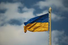 Flag of Ukraine against the background of cloudy sky - stock photo