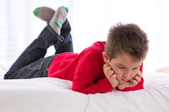 Unhappy kid looking down Stock Photos
