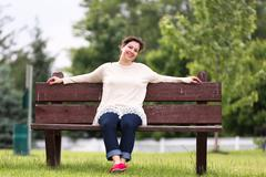 woman on bench expressing her positivity - stock photo