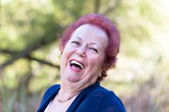 enthusiastic senior woman giving a genuine laugh - stock photo
