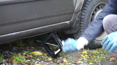 Man using a jack for putting car down Stock Footage