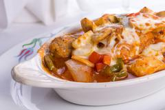 chicken saute baked in oven in oval dish cheese melted on top of it - stock photo