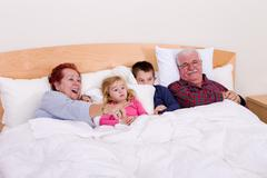 Grandparents watching tv in the bed with their grand kids Stock Photos