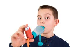 kid using inhaler with spacer - stock photo