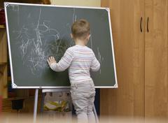 Little boy drawing on a chalkboard at kindergarten Stock Photos