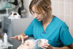 Nurse in a skin clinic applying protective cream - stock photo