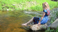 Girl sitting big rock with foot splash spray stream water smiles Stock Footage