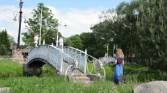 Beautiful white painted ornate bridge over the river girl goes Stock Footage