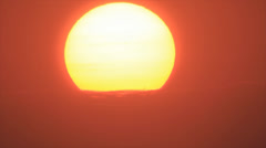 Dipping sun disk in blind clouds Stock Footage