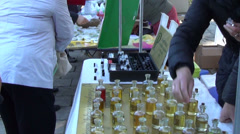Zoom out of vendor sell scents perfume in retail market fair Stock Footage
