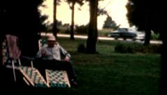 vintage 1960s male sits down to relax in a lawnchair car passing outdoors shade - stock footage