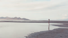 One Girl Standing On An Empty Beach - Viewed From A Distance Stock Footage