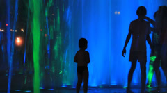 Silhouettes people on background fountain light show Stock Footage