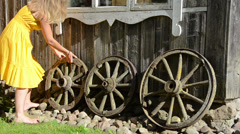Woman adjust old cart wheels decorations near rural house Stock Footage