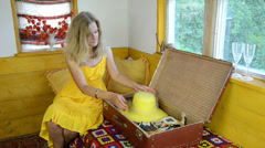 Peasant woman finishes packing suitcase puts yellow straw hat Stock Footage