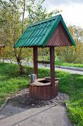 countryside water well with a bucket. - stock photo