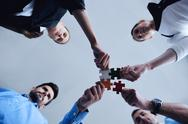 Stock Photo of group of business people assembling jigsaw puzzle