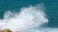 A marine wave breaks against off-shore stone Stock Photos