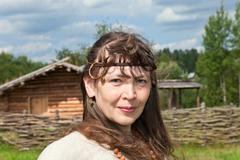 woman in an old traditional russian dress on a background of 10th century vil - stock photo