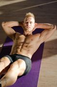 handsome young man doing abs exercises on mat - stock photo