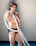 muscular man nude with heavy, big rope in his arms - stock photo